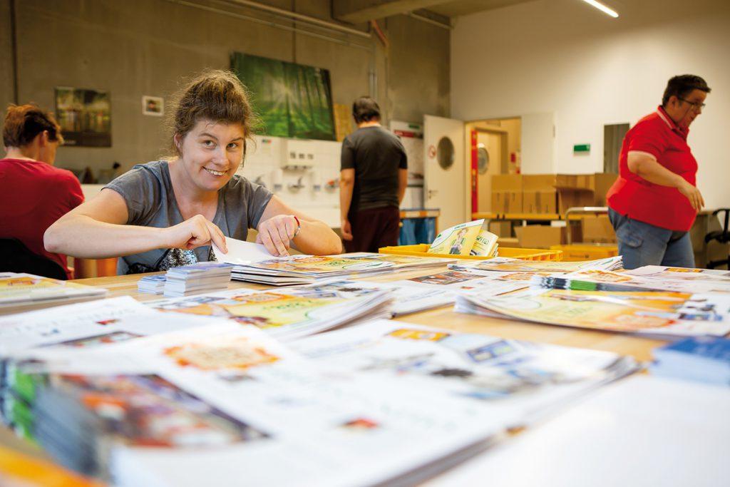 Junge Frau mit Beeinträchtigung in Druckerei