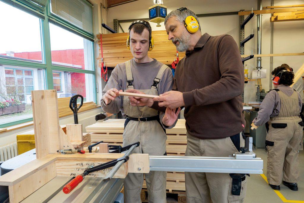 Ausbilder mit jungen Mann mit Beeinträchtigung in Holzwerkstatt