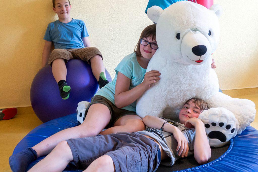 Drei Kinder mit Riesen Kuscheltier