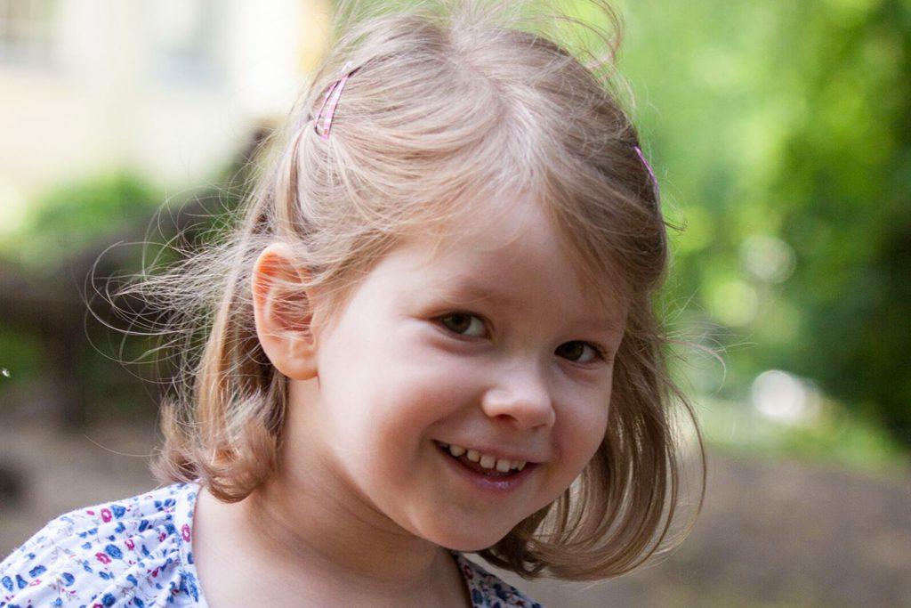 kleines Mädchen lacht in die Kamera
