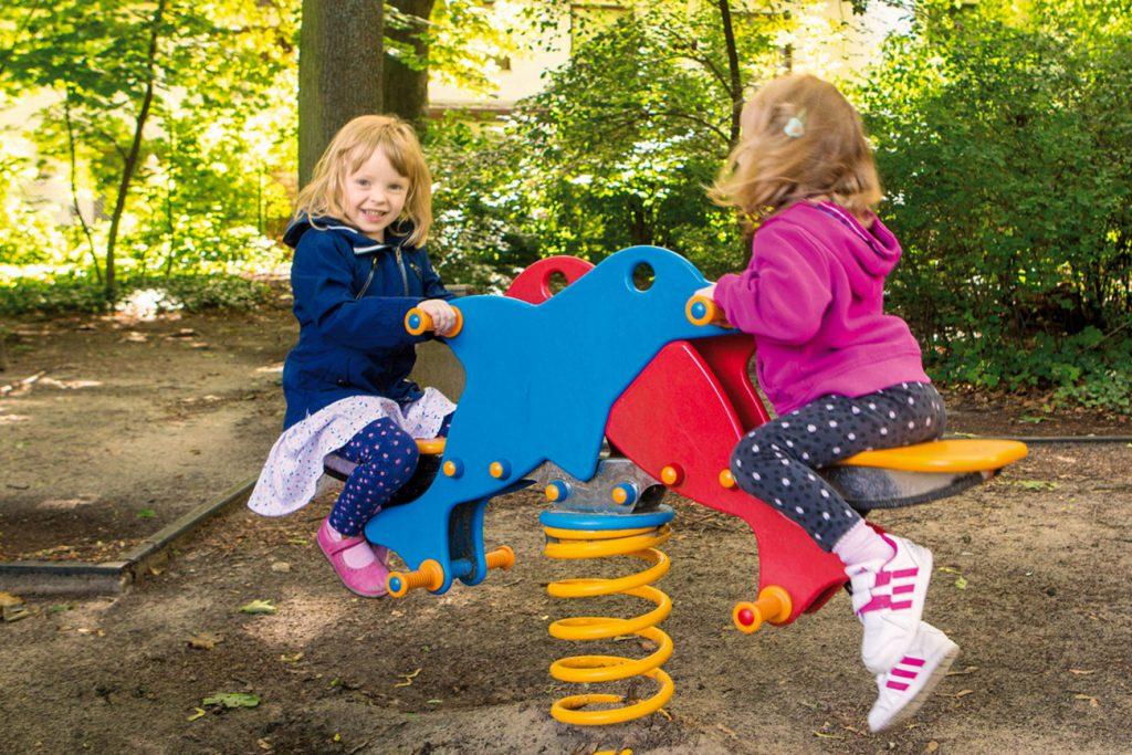 Zwei kleine Mädchen auf Schaukelpferden