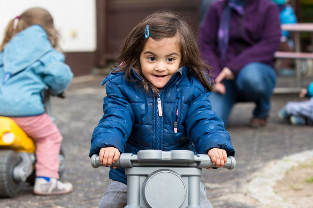 Mädchen mit Spielzeugmotorrad