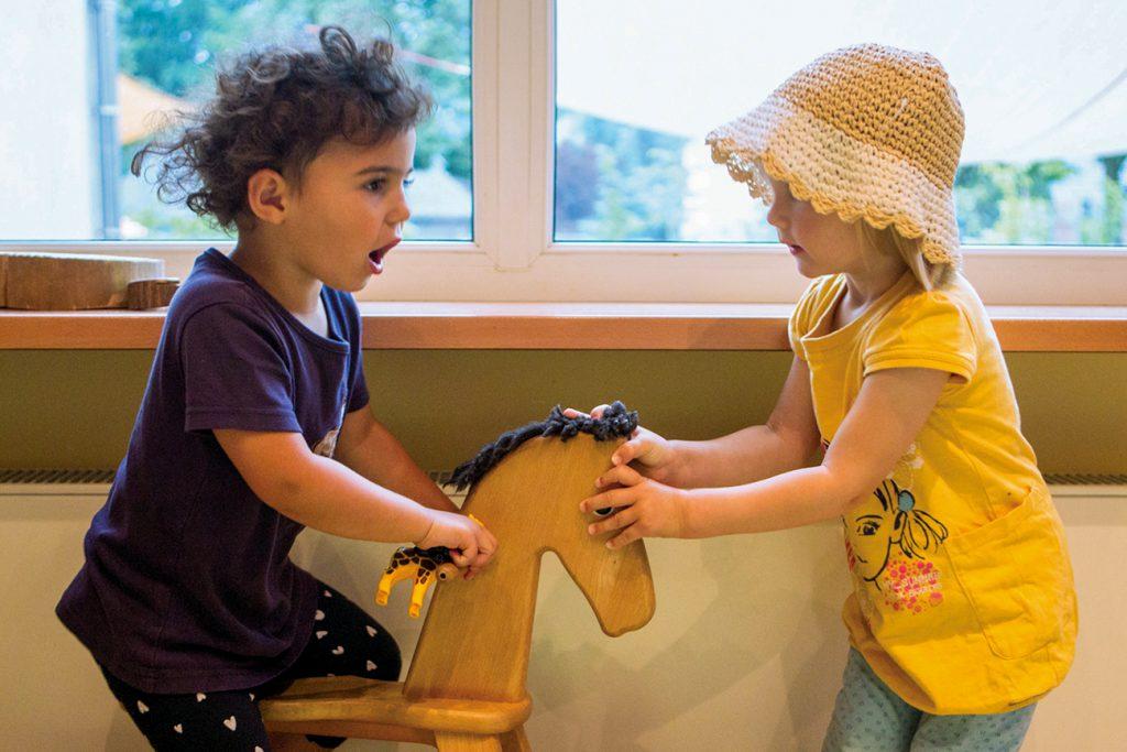 zwei kleine Mädchen mit Schaukelpferd
